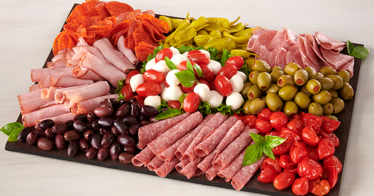 Antipasto tray witb lunch meats, olives, cheese, peppers and tomatoes