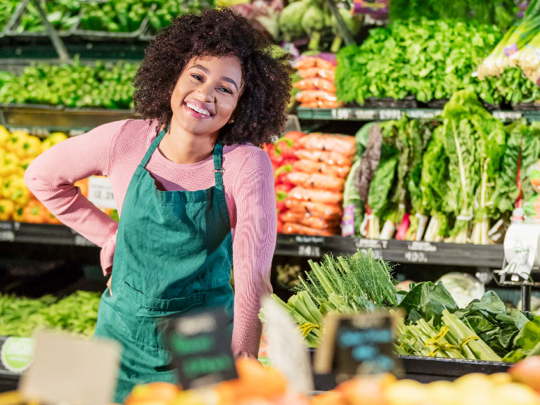 Girl super market employee in produce section