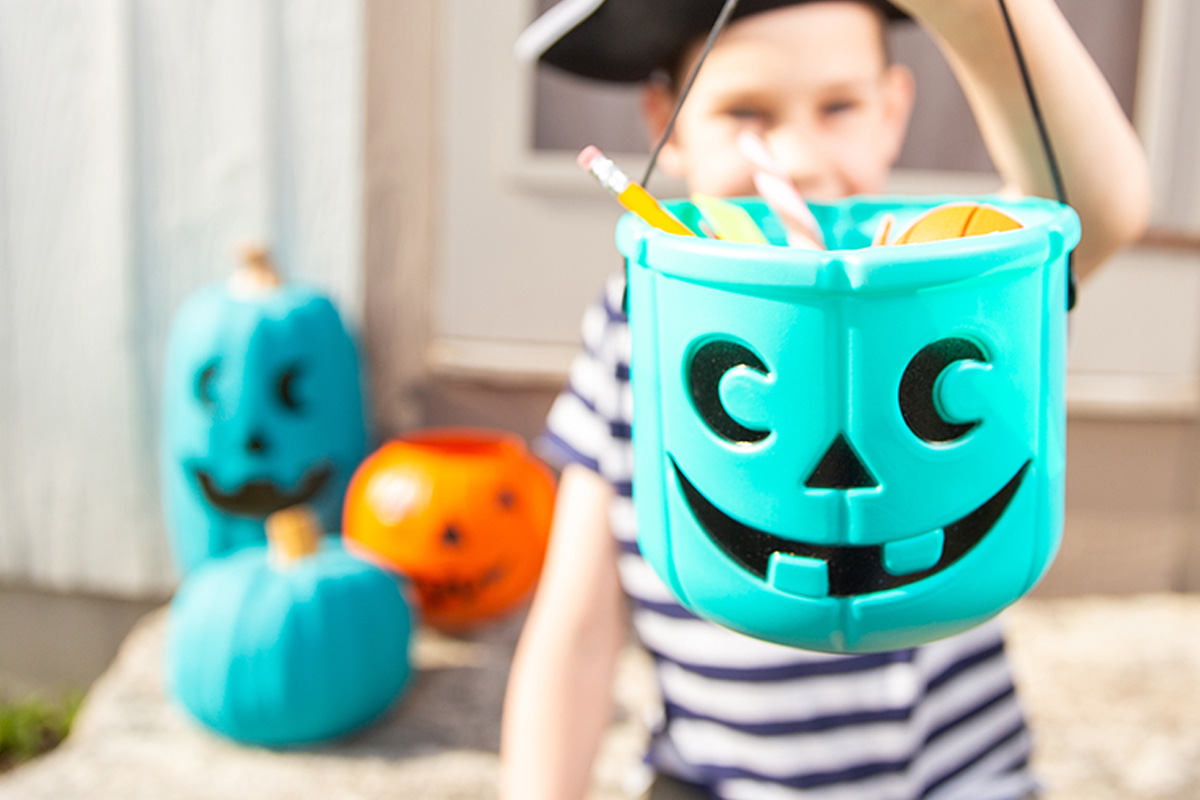 teal pumpkin on porch with kid holding teal pumpkin goodies