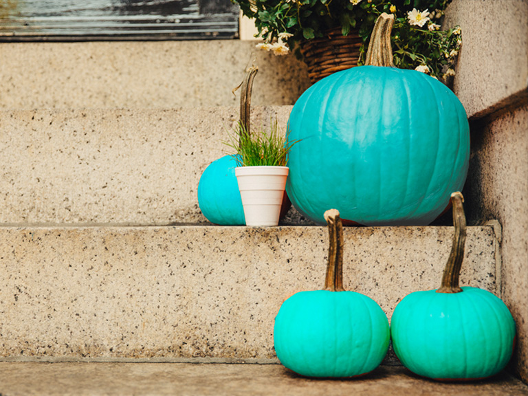 Teal pumpkins on porch steps.