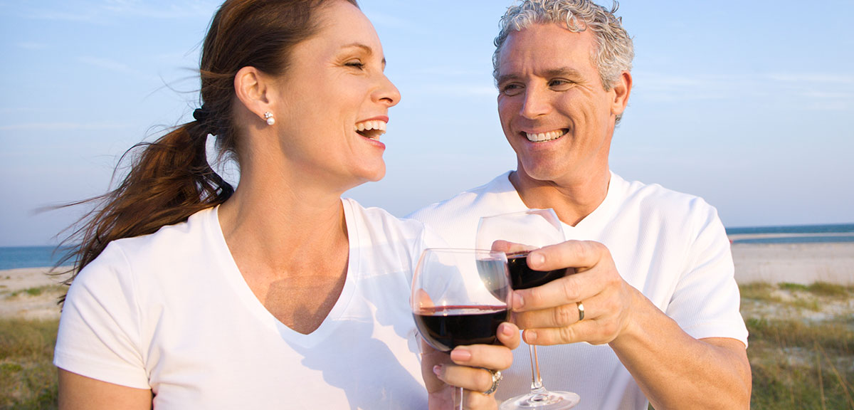 man and women drinking red wine with lake in the background