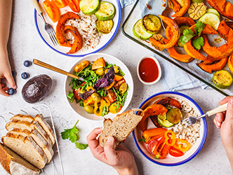 Table top with bowls of vegetables and person lifting up forkful of rice