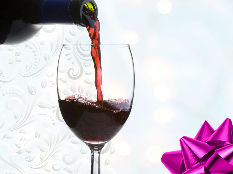 wine pouring into glass with holiday theme and violet colored bow